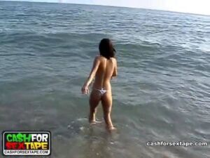 Slim cutie bounding into the sea in nothing but skimpy panties
