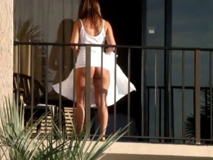 Woman without panties on hotel balcony