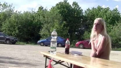 Naked girl having lunch at picnic table